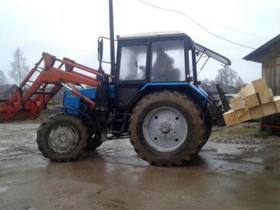 Трактор с фронтальным погрузчиком МТЗ-82 грузит брус